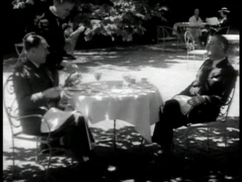 vídeos de stock e filmes b-roll de ext amp garden of upscale private club sir wilmot lewis of london times seated in garden w/ arthur krock lewis talking about father coughlin krock... - 1935