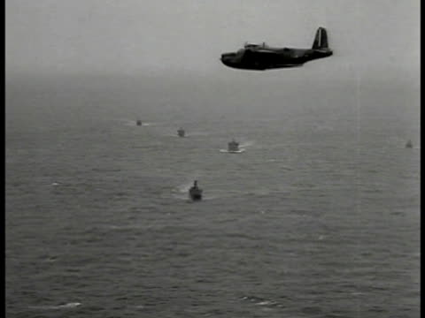 vidéos et rushes de ms british navy battleships at sea aerial raf sunderland mark i 'flying boat' patrol bomber flying over convoy of battleships ha british battleships... - 1941