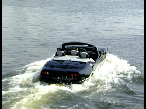 vídeos de stock, filmes e b-roll de london new amphibious car the gibbs aquada driven down ramp and into water pan tbv car away thru water pan lbv car along thru water at speed pan lms... - veículo anfíbio