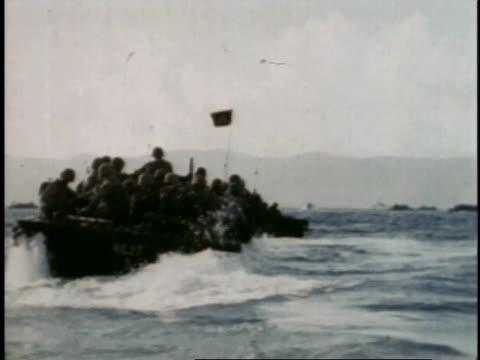 amphibious craft emerging from ship, carrying marines toward beach / guam - guam video stock e b–roll