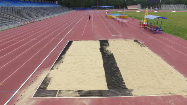 amputee athlete practicing long jump, aerial view - salto in lungo video stock e b–roll