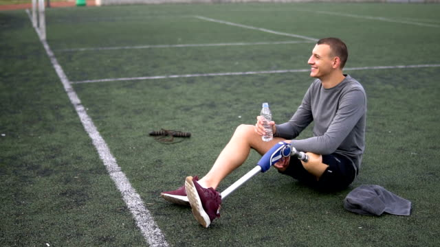 Amputee athlete relaxing and drinking water after training