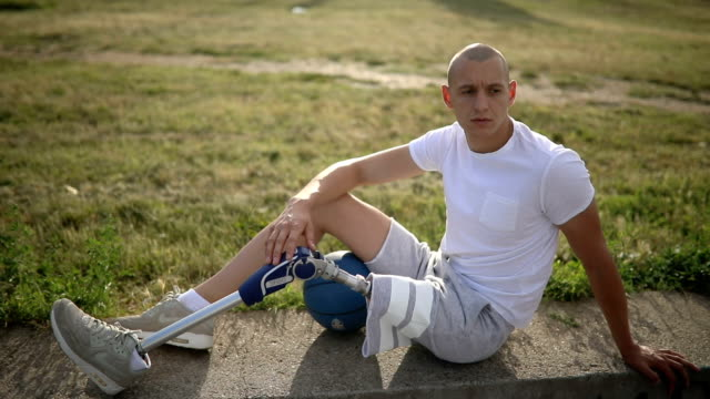 amputee athlete relaxing by the basketball court - amputee stock videos & royalty-free footage