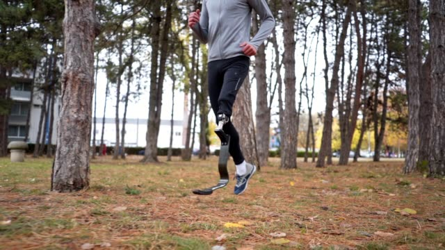 amputee athlete running in a city forest - artificial limb stock videos & royalty-free footage