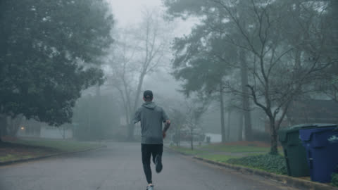 stockvideo's en b-roll-footage met amputee athlete runs down a residental road early in the morning - athleticism
