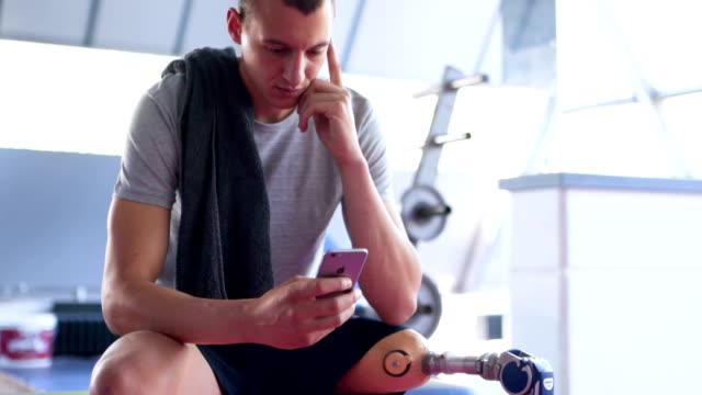 amputierter athlet sms in der turnhalle - künstliches gliedmaß stock-videos und b-roll-filmmaterial