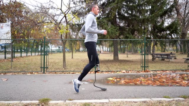 amputee athlete with a artificial leg running in autumn - artificial limb stock videos & royalty-free footage