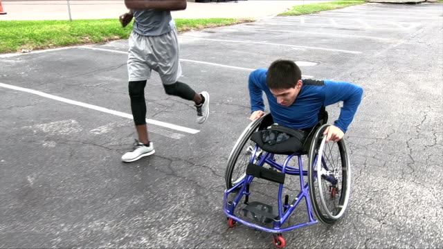 amputee in wheelchair, friend running beside - conquering adversity stock videos & royalty-free footage