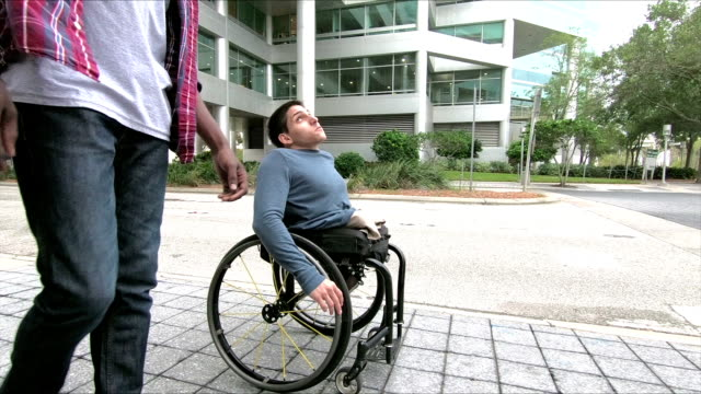 amputee in wheelchair talking with his friend - only young men stock videos & royalty-free footage