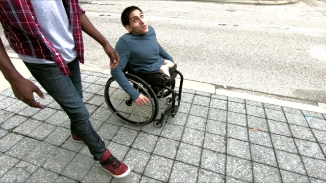 Amputee in wheelchair talking with his friend