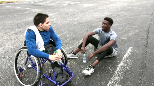 amputee in wheelchair, tired from exercise, with friend - amputee stock videos & royalty-free footage