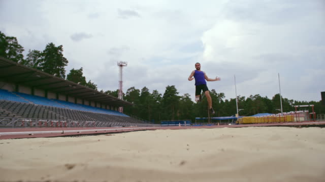 amputee long jumper kicking up sand - salto in lungo video stock e b–roll