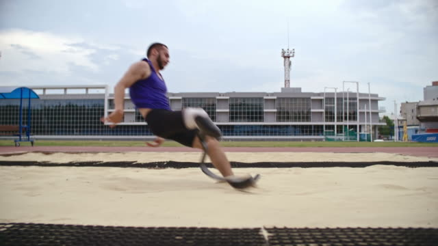 Amputee long jumper landing in sand