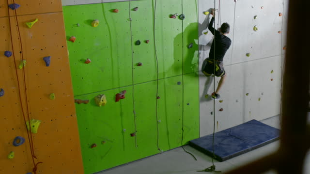 Amputee man without leg going up on climbing wall