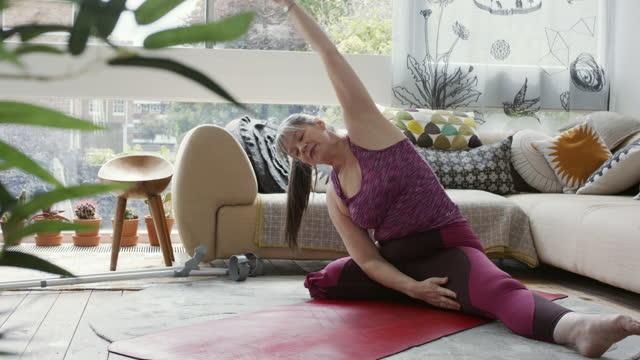 amputee mature woman in leotard practising yoga in sitting room - leotard stock videos & royalty-free footage