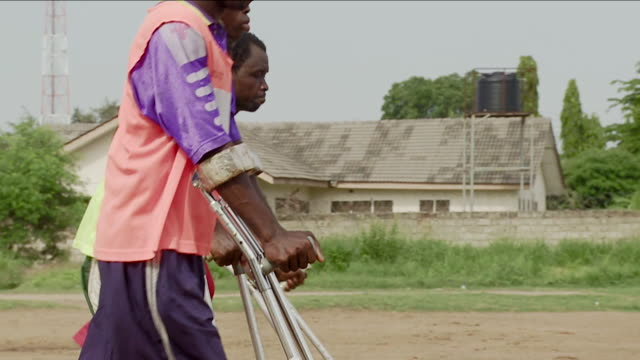 Amputee soccer players walk around a dusty pitch on crutches. Available in HD.
