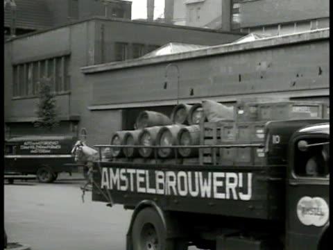 vídeos de stock, filmes e b-roll de ms 'amstel' truck carrying barrels of beer passing brewer ha ms dutch men stacking barrels into barge cu crates 'amstel dutch beer' brewery heineken... - 1947