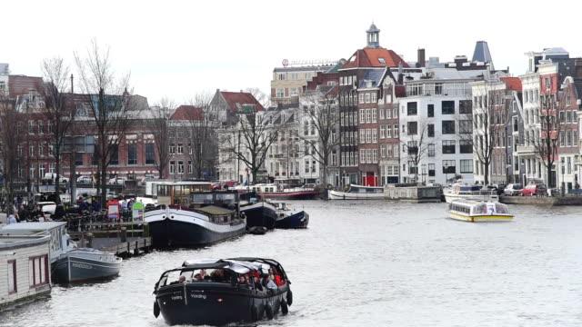 オランダのアムステルダム運河、北のオランダ王国。州立博物館タワー ビュー。ストリート、アムステルダム運河、自転車、自転車、屋形船、船の生活は。 - 北ホラント州点の映像素材/bロール