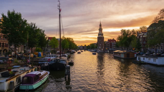 amsterdam canal with montelbaanstoren tower during sunset - 4k time-lapse - clock tower stock videos & royalty-free footage