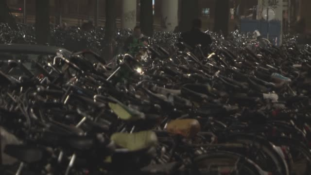 stockvideo's en b-roll-footage met amsterdam centraal station bike racks at night - infaden