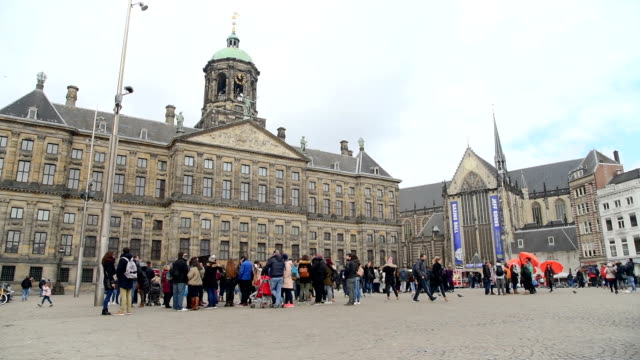 Amsterdam Dam Square and royal palace  tourists walk on the street (ED)