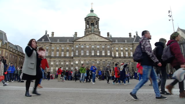 Amsterdam Dam Square and royal palace  tourists walk on the street