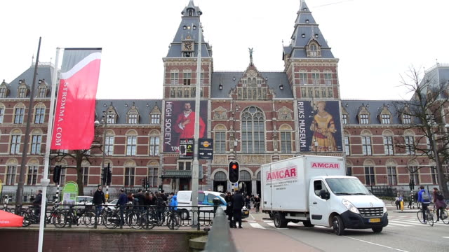 Amsterdam outside Rijksmuseum tourists walk on the street