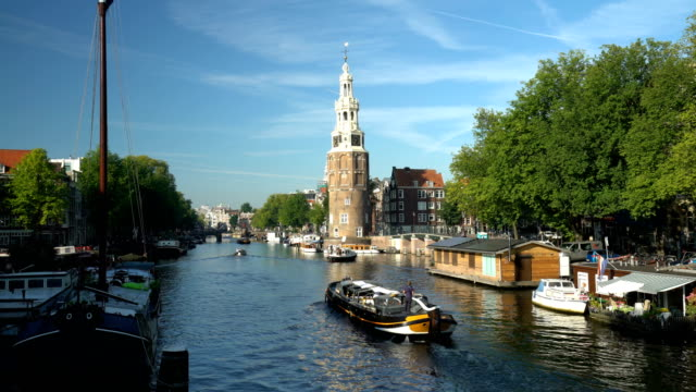 vídeos de stock e filmes b-roll de amsterdam skyline with canal and old tower, time lapse - barco casa