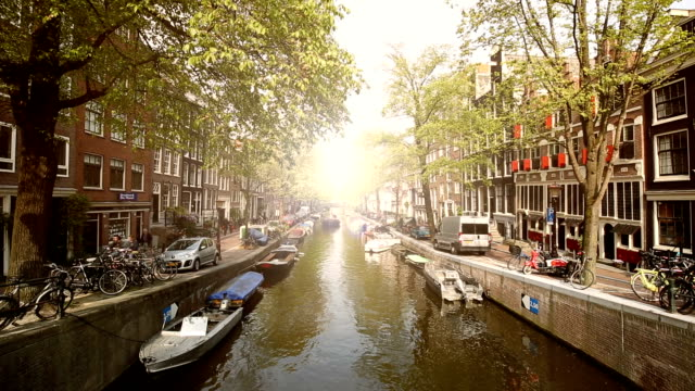 amsterdam skyline with canal and sun - amsterdam stock videos & royalty-free footage