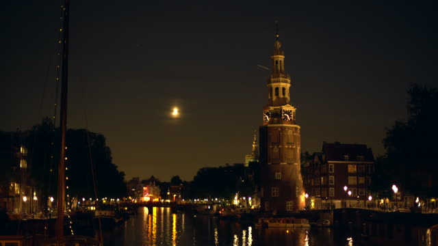 amsterdam with canal and old tower, panning - amsterdam stock videos & royalty-free footage