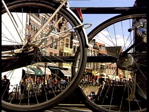 ls woman stands next to parked bikes on bridge over canal la ms canalside buildings seen through spokes of parked bicycles in f/g la ls church roof... - olanda settentrionale video stock e b–roll