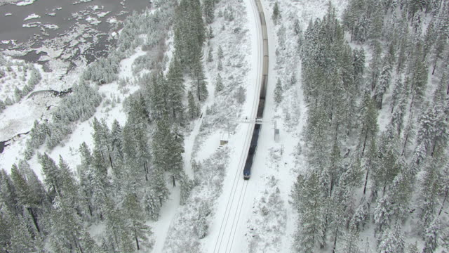 WS TS ZO AERIAL POV Amtrak locomotives pulling passenger train passing through snow covered pine forest with frozen small lake at Donner Pass in northern Sierra Nevada / Truckee, California, United States