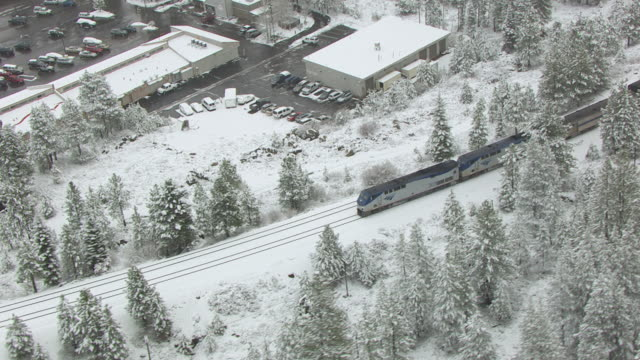 WS TS AERIAL POV Amtrak locomotives pulling passenger train passing through snow covered pine forest in northern Sierra Nevada with shopping area in background / Truckee, California, United States
