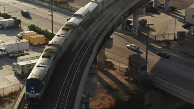 vidéos et rushes de amtrak train crossing bridge in industrial area - aerial - wagon