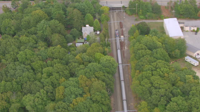 WS AERIAL POV Amtrak train moving over railway track through tree area / Niantic, Connecticut, United States