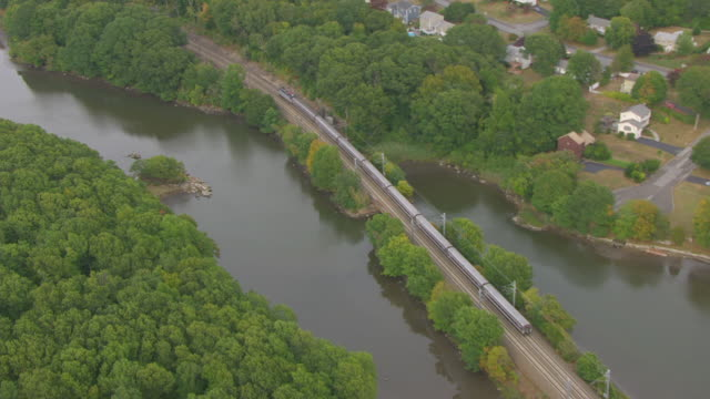 WS AERIAL POV Amtrak train moving over the railway bridge / Niantic, Connecticut, United States