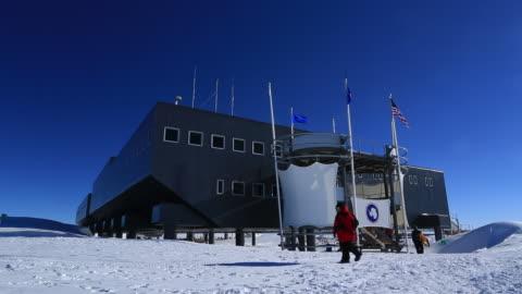 vidéos et rushes de amundsen-scott south pole station with scientists and tourists walking out (unrecognisable) - pôle sud