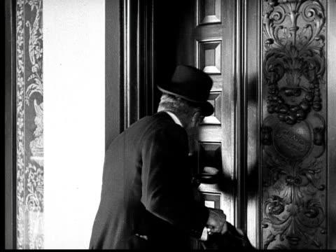 vídeos de stock e filmes b-roll de b/w, ms, amused cowboy (will rogers) assisting king sneaking home late, 1924 - ir em frente