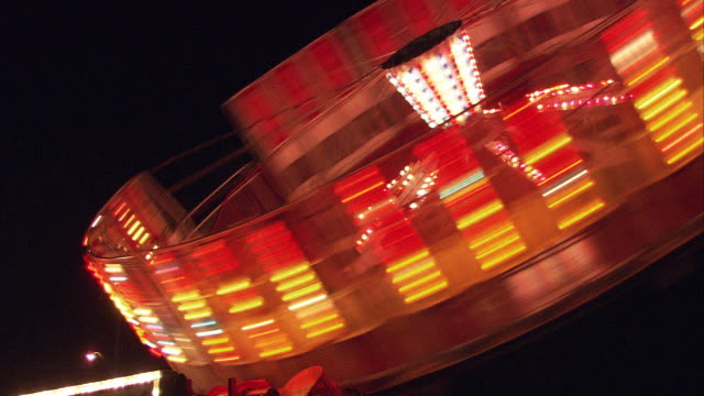cu amusement park ride spinning at night / hartsdale, new york, usa - fairground ride stock videos & royalty-free footage