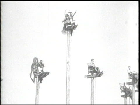 / amusement park with tall poles each with a person siting on top of a little chair / flagpole sitters waving pulling up box of supplies on rope jug... - jug stock videos & royalty-free footage