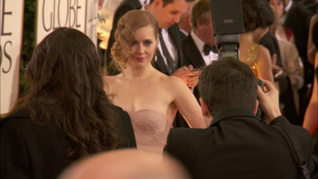 Amy Adams posing for paparazzi in crowd on the red carpet at the Beverly Hilton Hotel