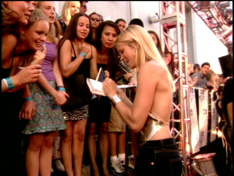 Amy Smart is signing autgoraphs for fans on the red carpet of the 2000 MTV Movie Awards