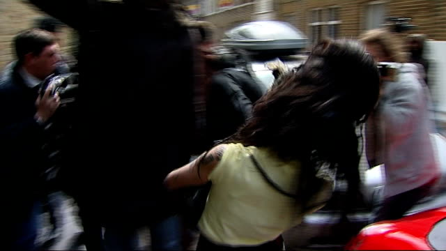 amy winehouse arrested on suspicion of assault; england: london: ext singer amy winehouse along from house to car as pursued by press sot - amy winehouse stock-videos und b-roll-filmmaterial