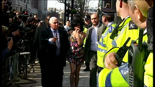London Westminster magistrates' Court EXT Amy Winehouse arrival at court with father Mitch Winehouse past press photographers Magistrates' Court sign...
