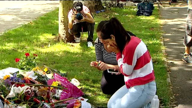 friends and fans pay tribute; england: london: ext side view of woman crying and wiping away tears with tissue close shot of tributes at makeshift... - amy winehouse stock-videos und b-roll-filmmaterial