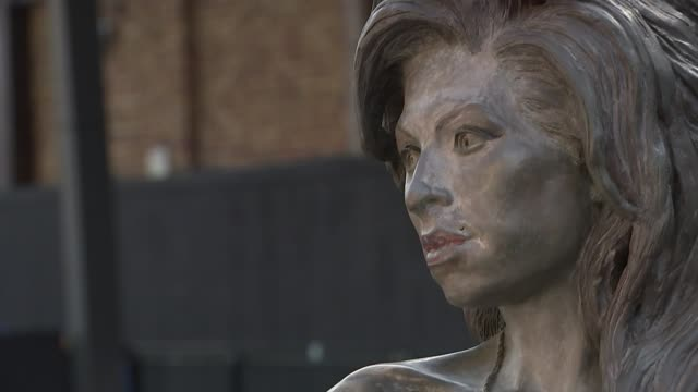 amy winehouse fans gather to remember late singer uk london camden market people posing with amy winehouse statue london camden market ext various of... - itv london tonight weekend点の映像素材/bロール