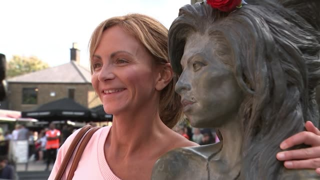 amy winehouse fans gather to remember late singer uk london camden market people posing with amy winehouse statue london camden market ext woman... - itv london tonight weekend点の映像素材/bロール