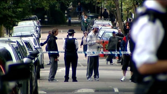 amy winehouse found dead: police, press and fans outside home; police officer beside 'camden square' sign / police cordon and people gathering on... - amy winehouse stock-videos und b-roll-filmmaterial
