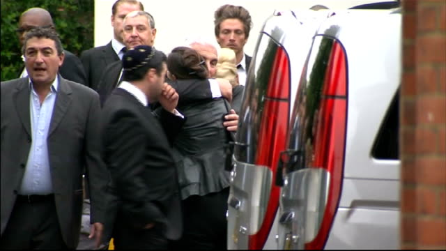 Amy Winehouse funeral Golders Green Crematorium Mitch Winehouse hugging unidentified woman outside Crematorium Close shot of unseen mourner carrying...