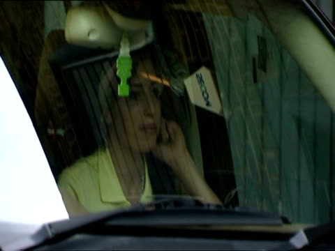amy winehouse sitting in minivan before leaving for police station to answer to assault charges on april 25 2008 / car driving away / london england... - black hair stock videos & royalty-free footage